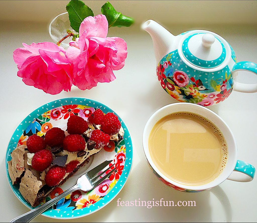 Fresh fruit topped meringue slice served with a pot of tea and flowers