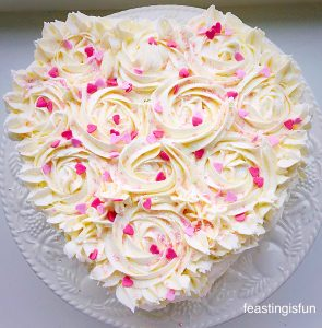 Heart shaped cake covered in piped buttercream roses and decorated with mini edible pink hearts.