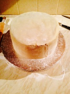 Use your hands to press and mould the marzipan to the cake.