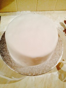 A beautifully fondant covered cake. Clean the board with a piece of damp kitchen towel.