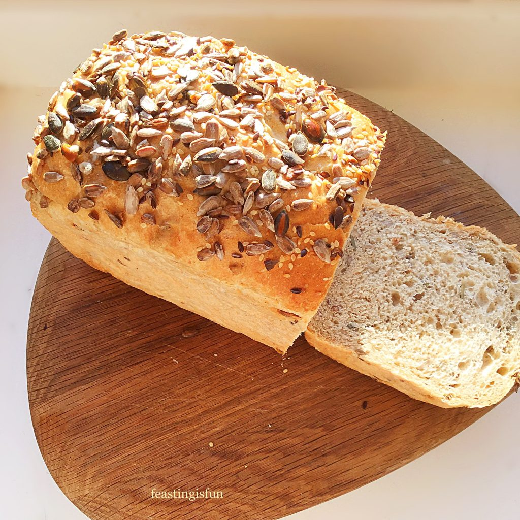 A sliced loaf of crunchy seeded bread on a wooden board.