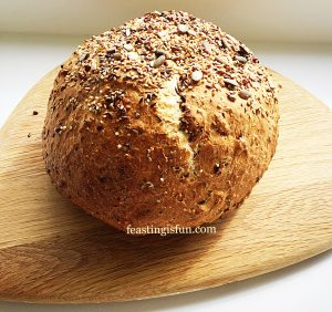 Seeded cob loaf of bread on a wooden board.