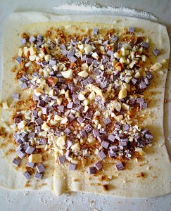 An even layer of sugar, chocolate and nuts spread over the rolled pastry.