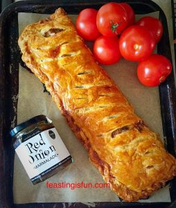 Sausage plait on a baking tray with fresh tomatoes and a jar of red onion marmalade from Hawkshead Relish.
