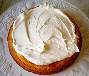 Spread half of the cream onto the bottom cake layer, flat side up.