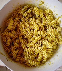 Add the jar of pesto sauce and mix thoroughly, ensuring all the warm pasta is coated.