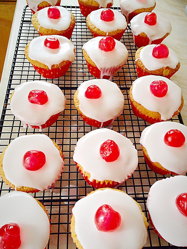 A cooling rack packed with red cherry topped Bakewell Cupcakes.