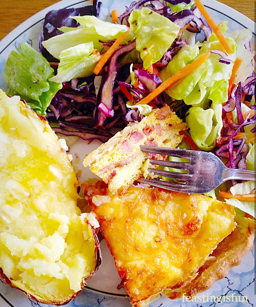 Cheddar, bacon and egg tart slice served on a plate with fresh salad and a baked potato.