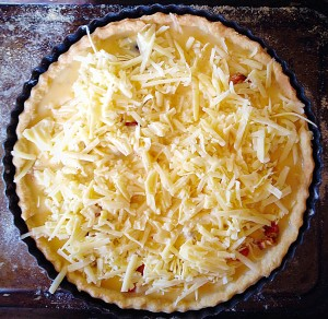 Slowly pour the egg mixture into the centre of the quiche, making sure that it doesn't flow over the top of the pastry.