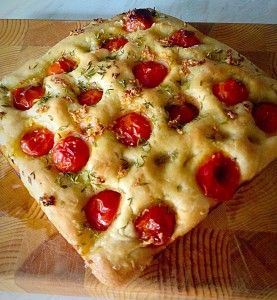 A wooden chopping board creates a fantastic background for this Tomato Thyme Focaccia Bread