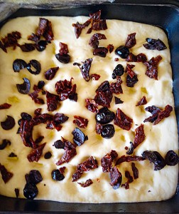 Sprinkle the chopped olives and sundried tomatoes evenly over the surface of the dough.