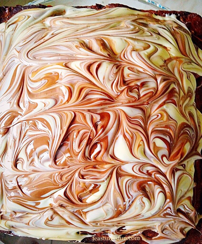 Close up of melted white and milk chocolate cake topping swirled together.