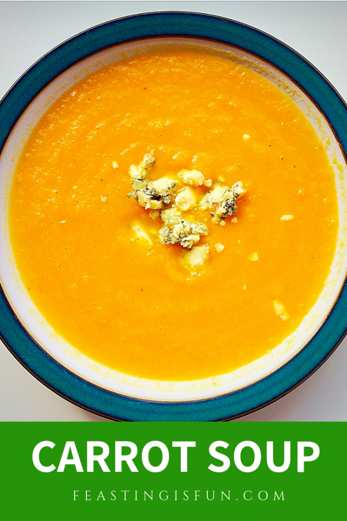 Pinterest sized image of carrot soup served in a green rimmed soup bowl.