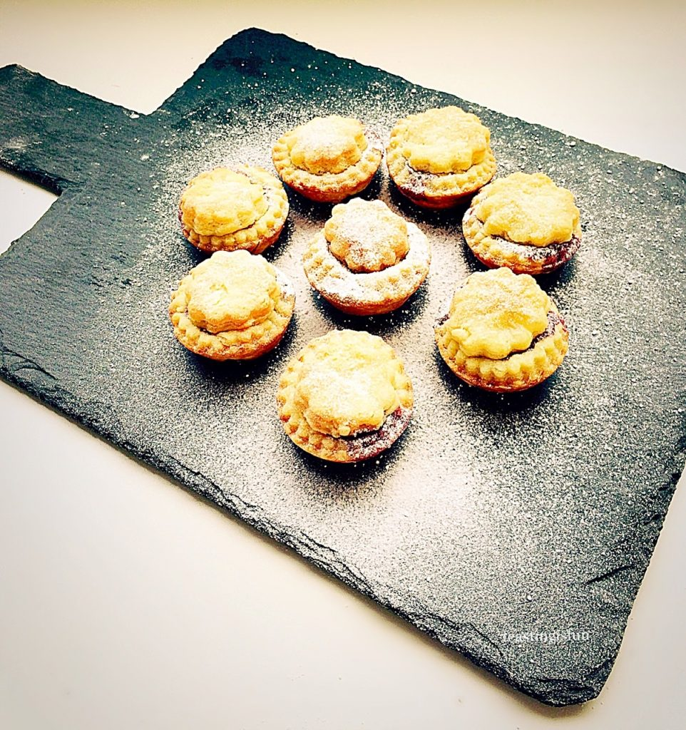 A snowy, icing sugar dusted platter of mince pies.