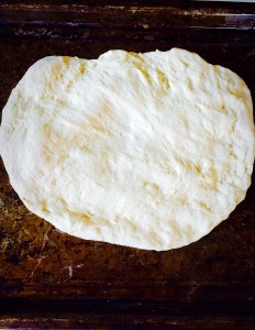 Work the dough with you hands on an oiled baking sheet. Start flattening and stretching the dough.