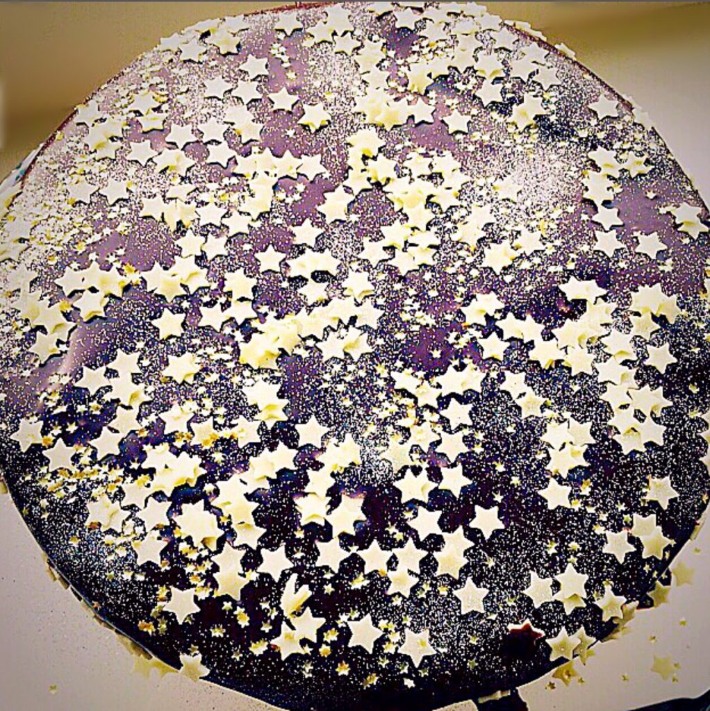 A chocolate cake decorated to look like a galaxy of stars.