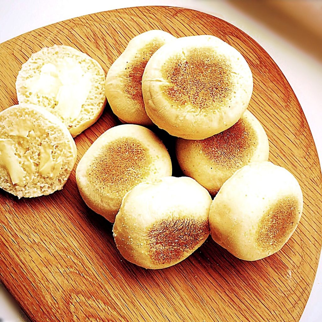 English muffins freshly baked on a wooden board.