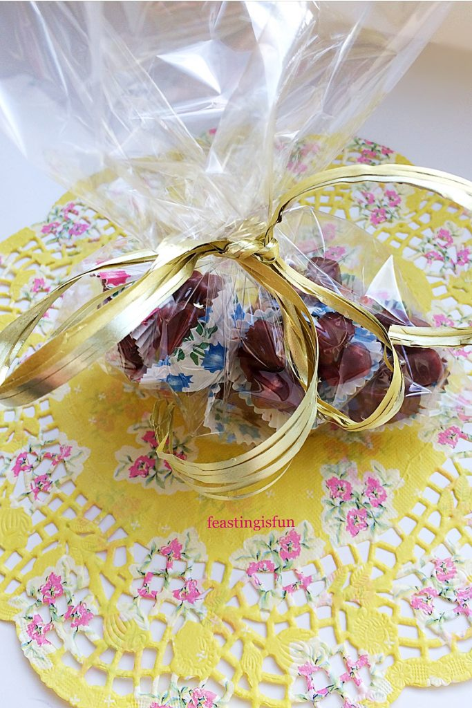 Rocky road petit fours wrapped in a cellophane bag and tied with gold raffia to give as a gift.