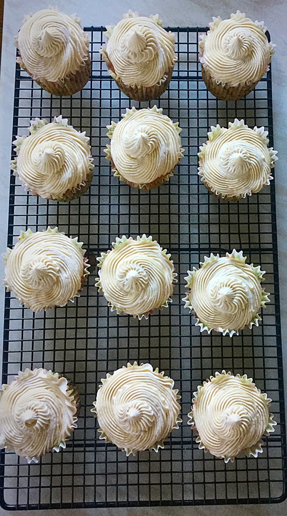 Vanilla Bean Cupcakes swirling, light buttercream, adorns the tops.