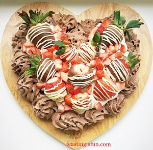 Chocolate heart shaped meringue covered in whipped cream and chocolate dipped strawberries.