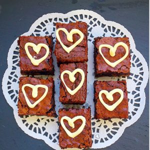 Small brownie squares decorated with a piped white chocolate heart.