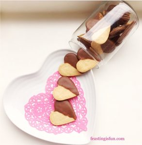 Chocolate heat cookies half coated in milk chocolate spilling out of a glass jar onto a pink heart doily.