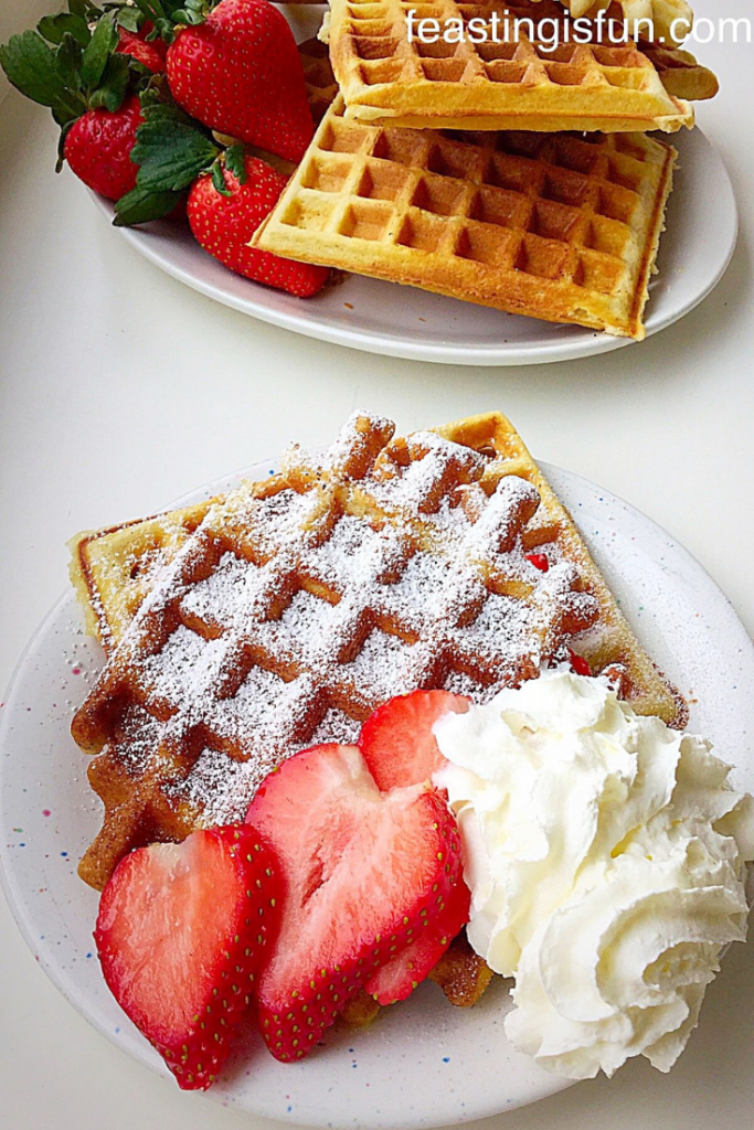 Two waffles on a plate in the foreground with a stack of waffles and strawberries in the background.