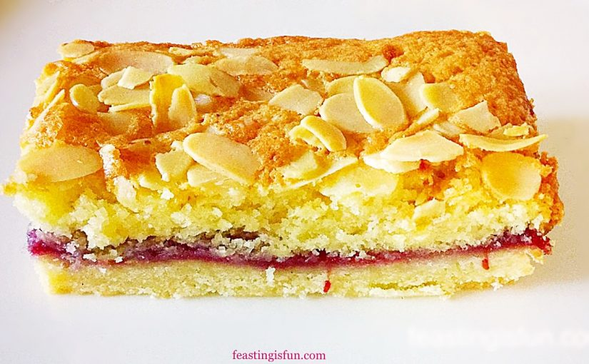 A slice of biscuit base topped with raspberry jam, then almond sponge and finished with flaked almonds on top. Each layer is clearly visible.