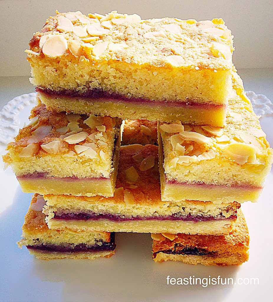 A stack of baked biscuit based, jam filled treats on a white plate.