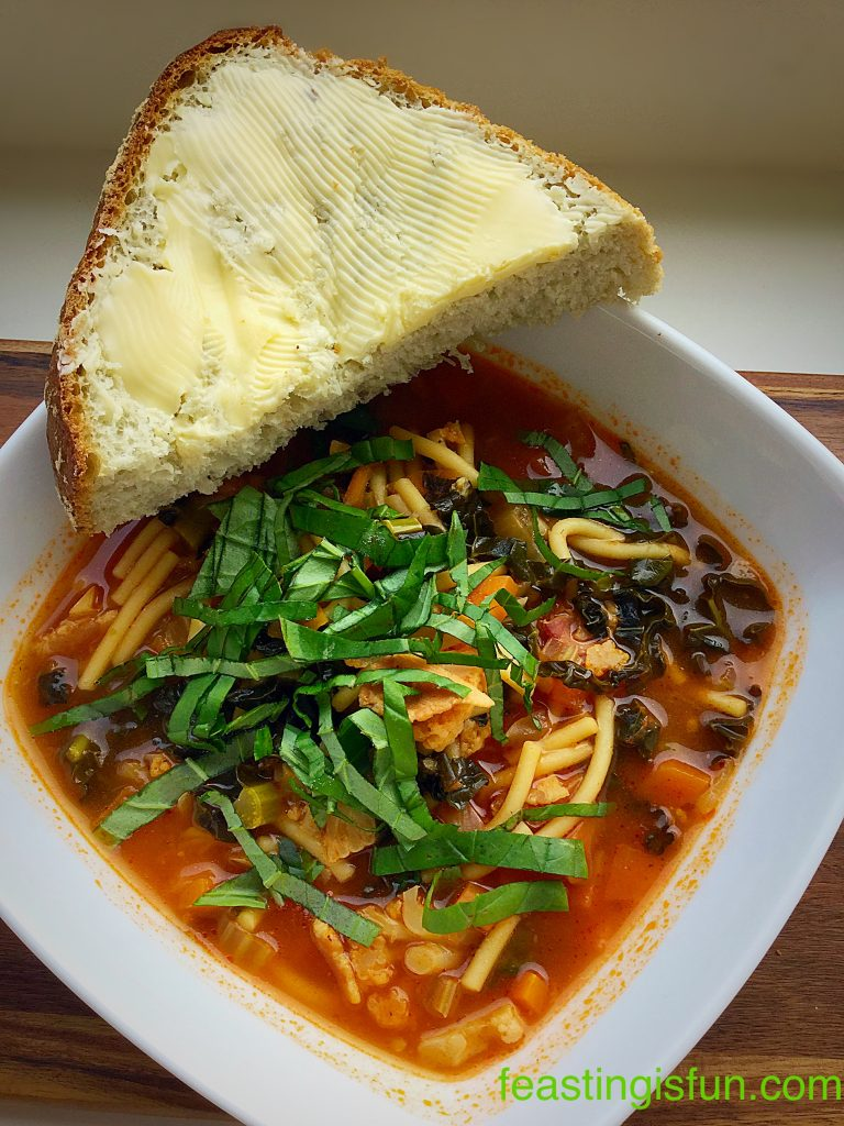 Hearty Minestrone Soup served with a thick slice of buttered, homemade bread.