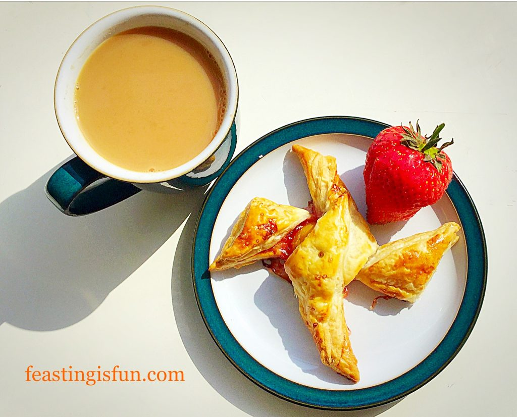 Unusual shaped fruit pastry on a plate with a mug of tea to one side.