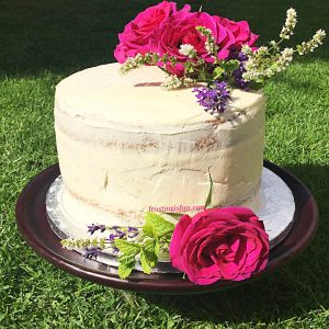 Vanilla buttercream covered sponge decorated with deep pink, fresh roses.