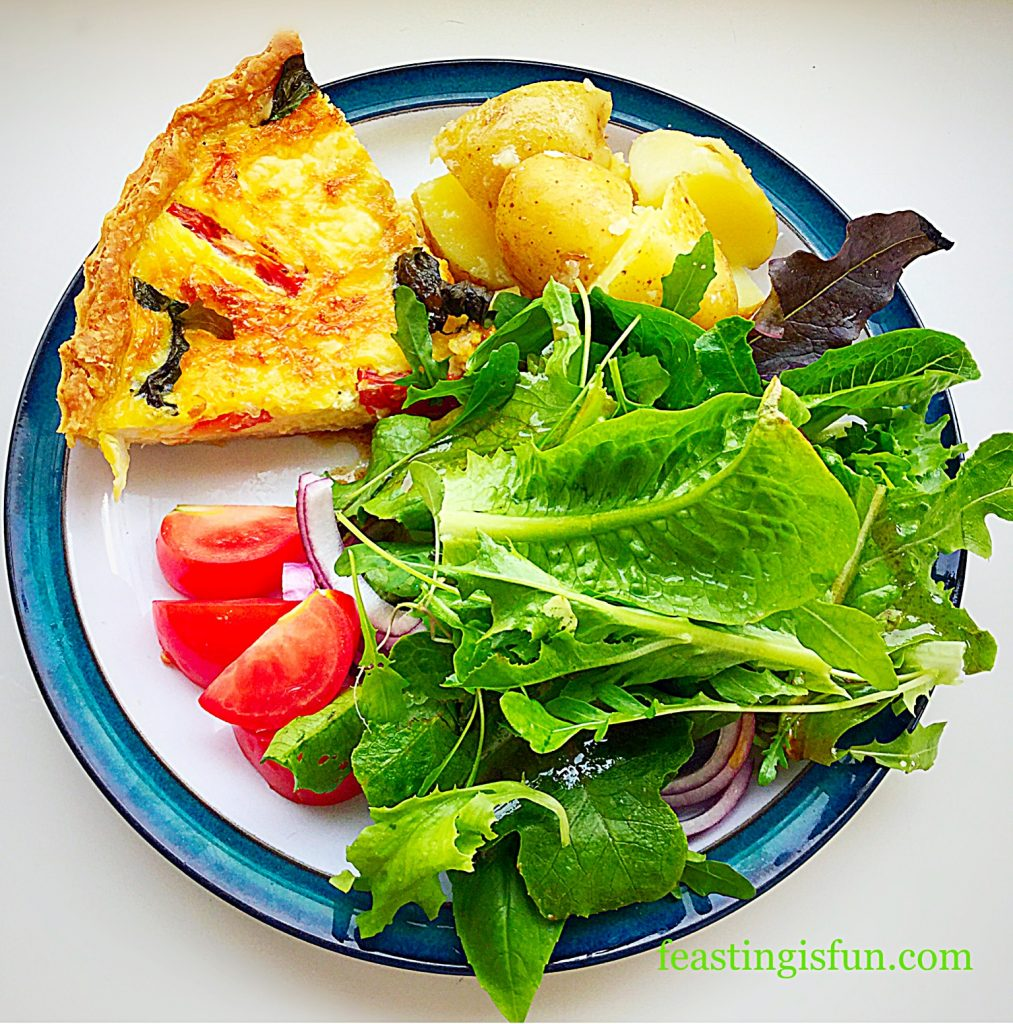 A portion of quiche served with new potatoes and salad leaves.