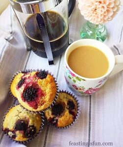 Blackberry oat muffins served with coffee in a lined tray.