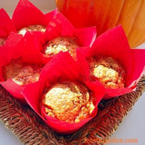 Individual autumnal squash breakfast bakes in red tulip wrappers, displayed in a rustic tray with a large orange, autumn squash in the background.