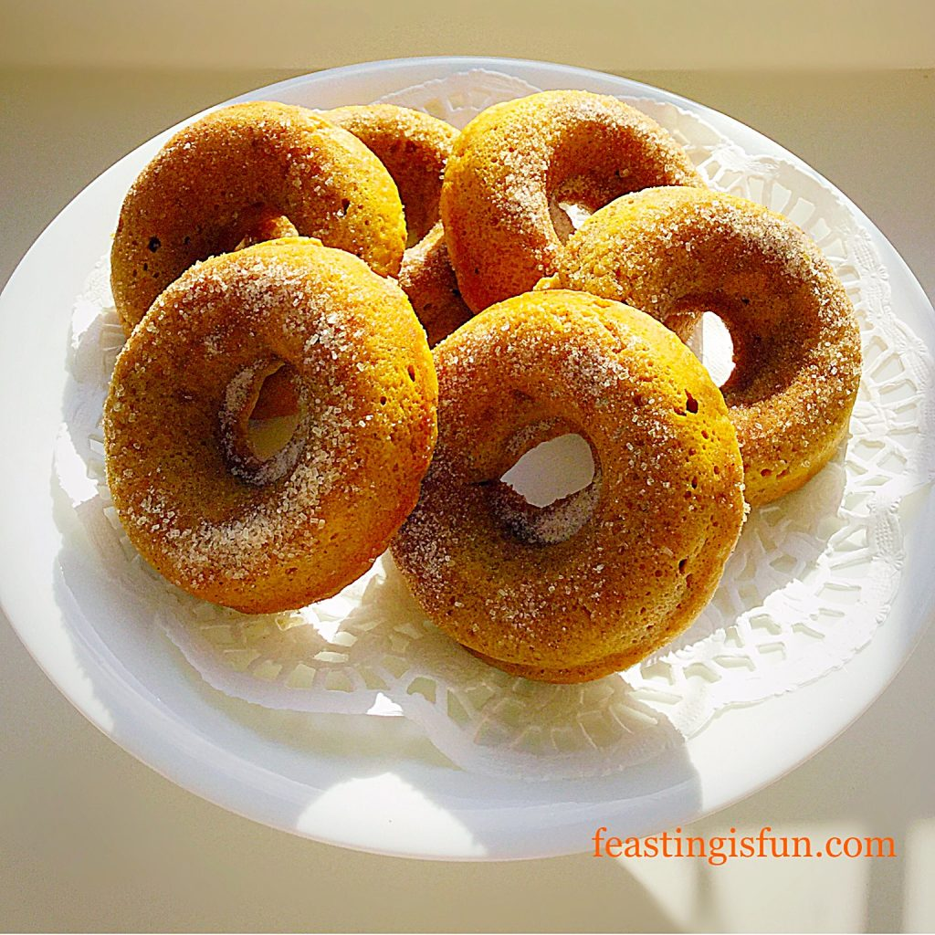 Autumn squash donuts displayed on a small white cake stand.