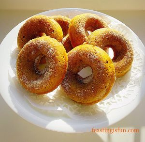 Baked pumpkin spiced doughnuts displayed on a cake stand.