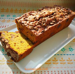Chocolate chip pumpkin loaf cake with one end sliced so the interior can be seen.