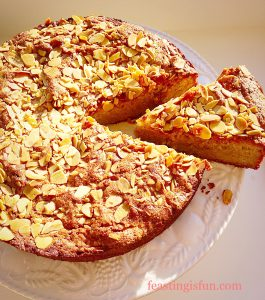 Gluten free large cake topped with flaked almonds. A slice is cut and pulled slightly away from the Autumn inspired cake.