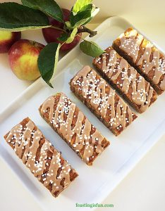 Fruit and nut cake bars drizzled with cinnamon icing and finished with contrasting white sugar nibs.