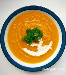 Roasted Garlic Butternut Squash Soup served in a bowl with curly parsley to garnish.