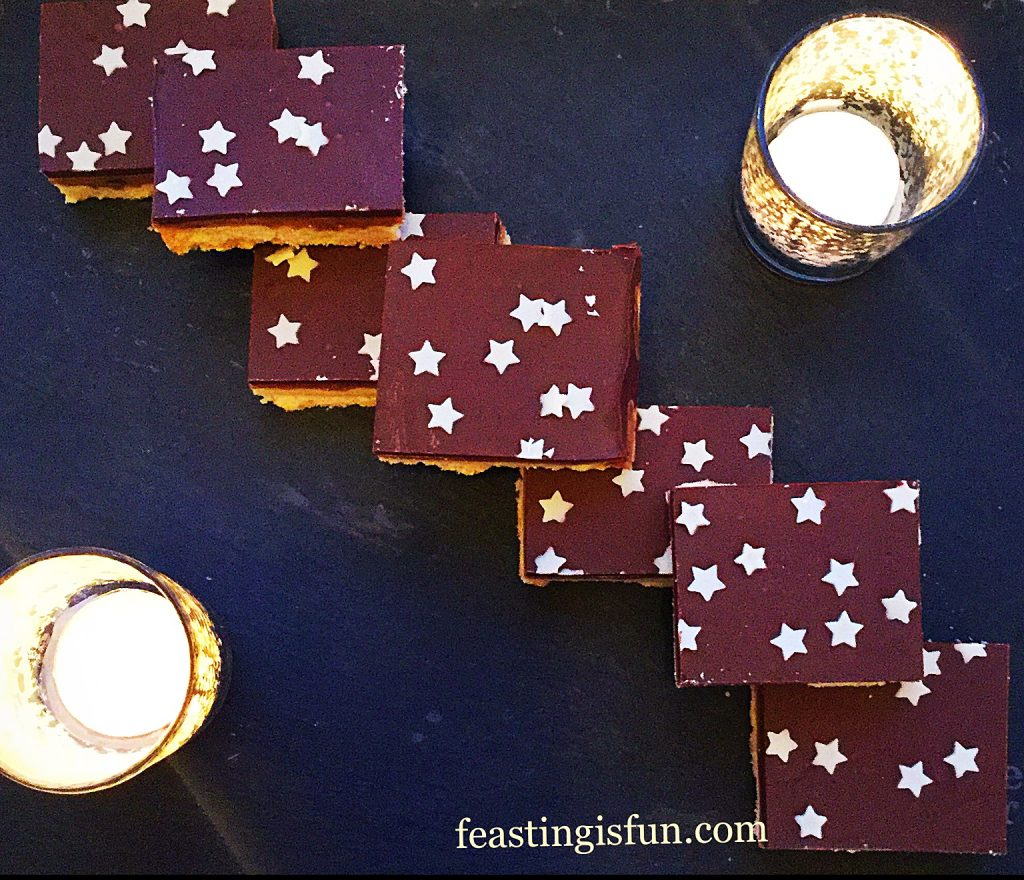Overhead image of festive sweet bakes decorated with white chocolate stars. Votive candles are placed on the slate platter.
