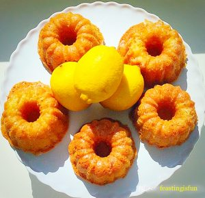 Mini lemon drizzle Bundt cakes on a white cake stand with fresh lemons.