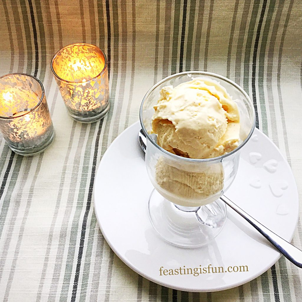 Frozen dessert scooped into a glass mug served on a white plate with a silver spoon.