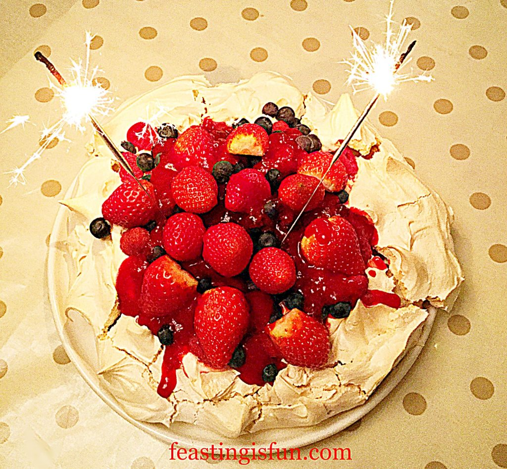 Fruit topped meringue dessert with indoor sparklers for celebrating.
