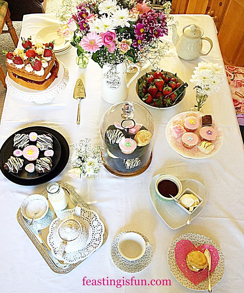 Afternoon Tea table laid out with cakes, tea, flowers, fruits and chocolates.