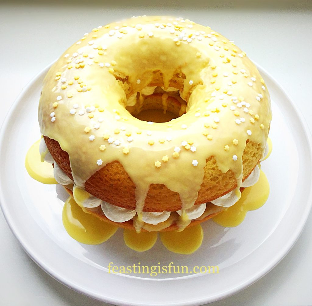 Large baked lemon doughnut filled with whipped cream and topped with a lemon drizzle icing.