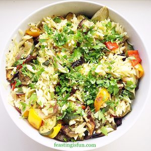 Roasted summer vegetable orzo pasta salad served in a white bowl and garnished with fresh, flat leaf parsley.