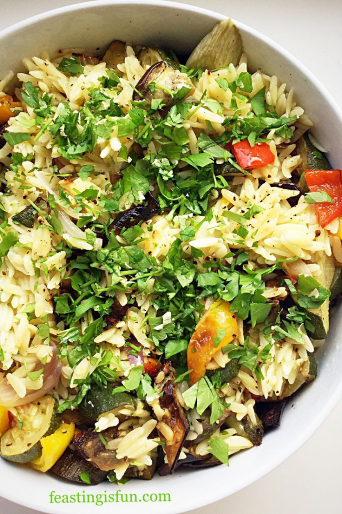 A bowl containing roasted vegetable pasta salad topped with chopped parsley.