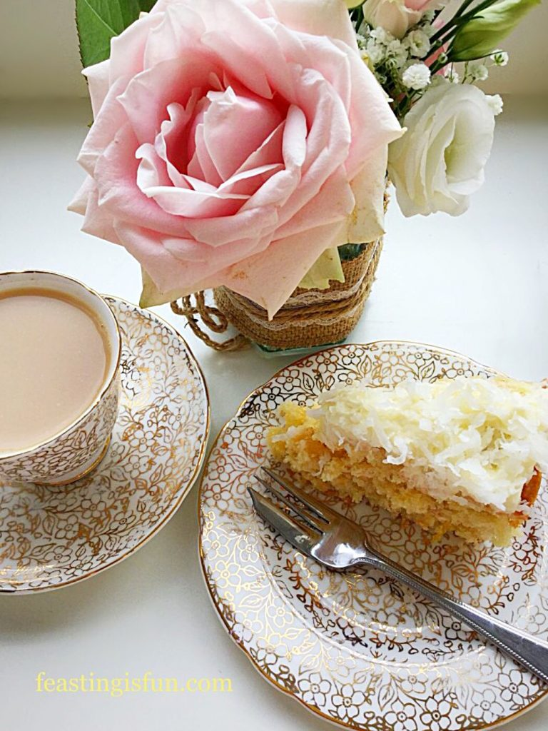 Afternoon tea set up with tea, cake and fresh flowers.